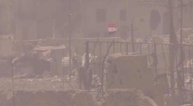 جندي يرفع العلم العراقي تحت النيران فوق أحد آخر معاقل داعش