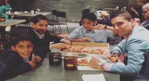 محمد عساف يتناول البيتزا مع أطفال