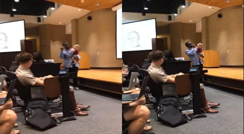 أستاذ جامعي يحمل طفل طالبته وهو يلقي محاضرته
