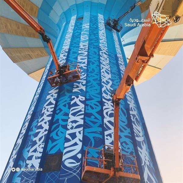 فنان يرسم لوحة فنية بالخط العربي على برج مياه الرياض