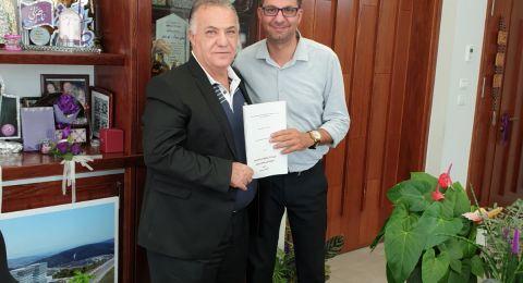 د. ناجي عباس يقدم ملخص رسالة الدكتوراه لرئيس بلدية الناصرة