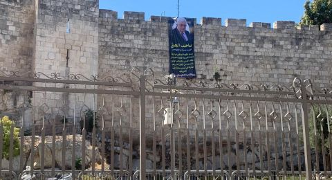 نشطاء يعلقون صورة أبو مازن على سور القدس تنديدا باتفاق التطبيع