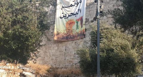 نشطاء مقدسيون يعلقون لافته على سور القدس ضد مؤتمر البحرين
