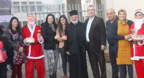 سخنين: الاب عارف يمين يشارك مدرسة الحلان باستقبال طلابها ومعلميها بحلويات بابا نويل