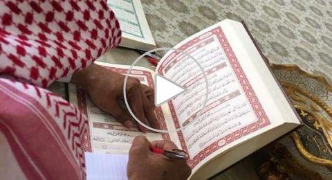 معلم سعودي يحتفي بانتهائه من نسخ المصحف الشريف