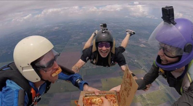 فريق قفز بالمظلات يتناول البيتزا في السماء على ارتفاع 14 ألف قدم
